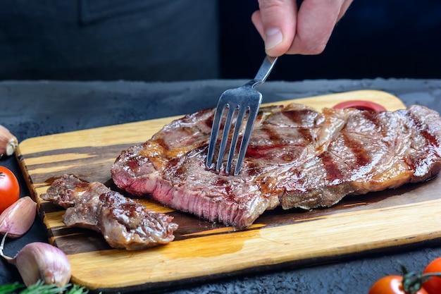 Рука держит вилкой стейк из мраморной говядины