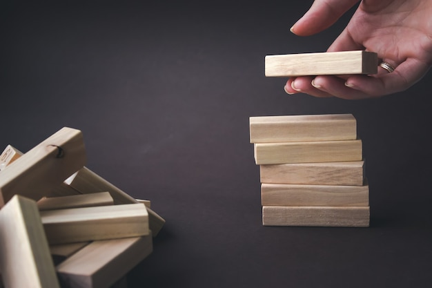 Hand holding a wood block on brown background. ladder career path concept for business growth succes