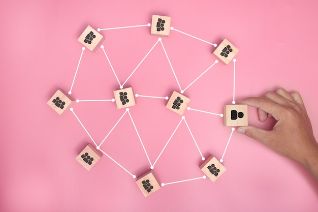 Hand holding wood blocks connected together on pink background. cooperation, teamwork, network and community concept.