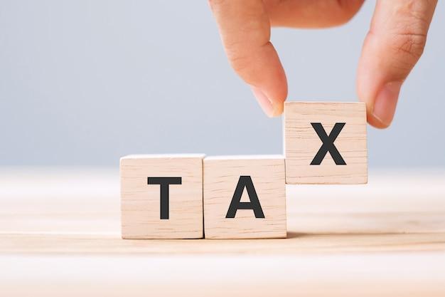 Taxテキストで木製の立方体ブロックを持っている手。財務、管理、経済、ビジネス、および課税までの時間の概念