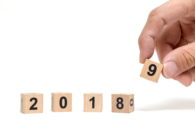 Hand holding wooden block 2019 on white background , happy new year concept