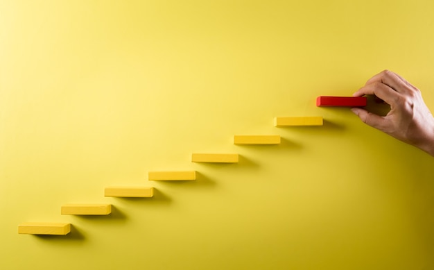 Рука, держащая штабелирование деревянных блоков как ступенчатую лестницу успех в концепции роста бизнеса