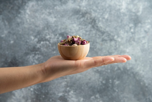 Hand holding a wooden bowl with dried roses.