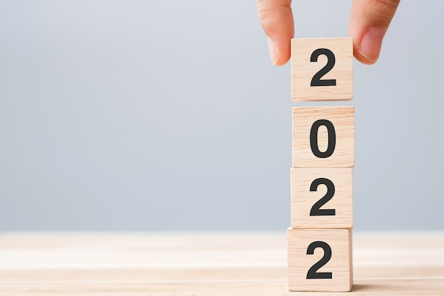 Рука деревянный кубик с текстом 2022 на фоне таблицы. решение, план, обзор, цель, начало и концепции новогодних праздников