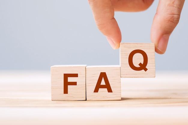 테이블 배경에 faq 텍스트(자주 묻는 질문)가 있는 나무 큐브 블록을 들고 있습니다. 금융, 마케팅 및 비즈니스 개념