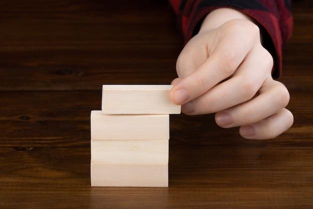 テーブルの背景にフリップオーバーブロックと木製の立方体を持っている手