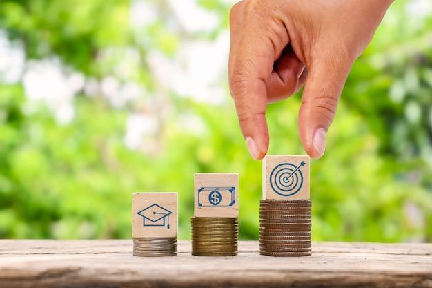 Рука держит деревянный куб с виртуальными целями на стопке монет