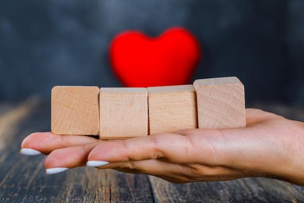 木製キューブを持っている手