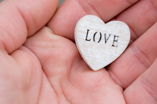 Hand holding a wooden heart with the lettering love sign of love in your hand