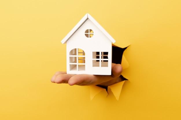 黄色の破れた紙から木造住宅モデルを持っている手。