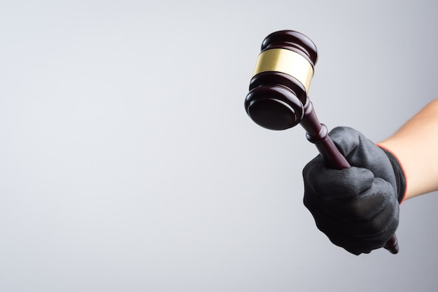 Hand holding wooden judge's gavel as a illegal or injustice sign