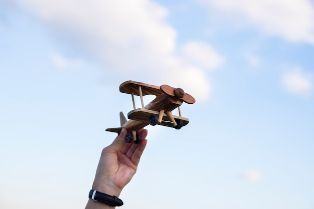 Hand holding a wooden plane sky background