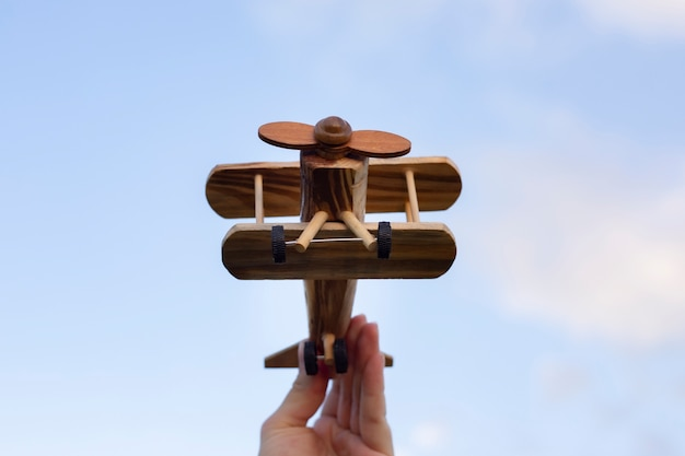 Hand holding a wooden plane vacation concept