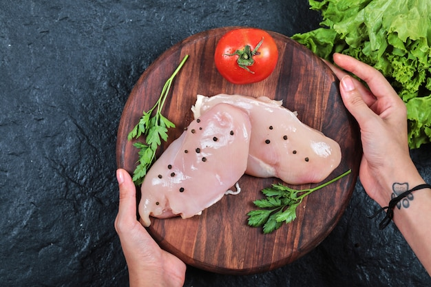 Hand holding wooden plate of raw chicken fillet with greens on dark table.