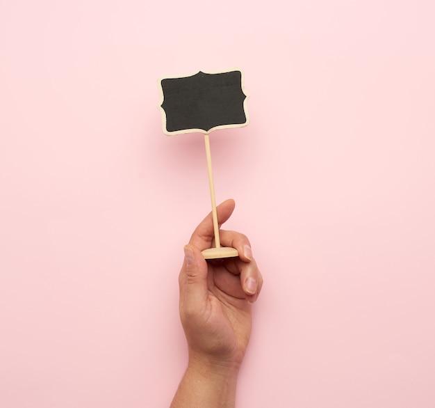 Рука деревянный указатель на палочке для написания текста, розовый фон