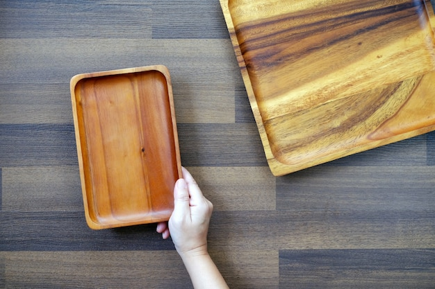 Hand holding wooden tray on table