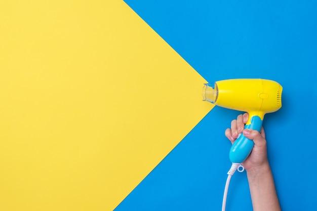 黄青色の表面に黄青色のヘアドライヤーを持っている手。カラフルな表面で髪を乾かすための装置。