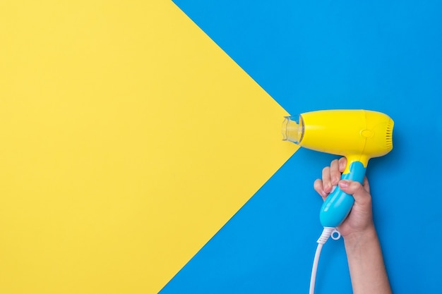 Hand holding yellow-blue hair dryer on yellow-blue surface. devices for drying hair on a colorful surface.