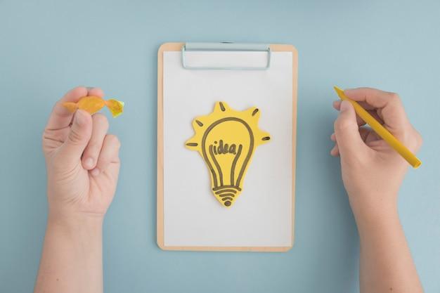 灰色の背景の上にクリップボードに黄色のクレヨンとチョコレートを描く電球を手に手