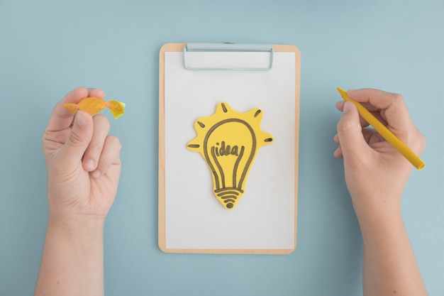 Hand holding yellow crayon and chocolate drawing light bulb on clipboard over the gray background