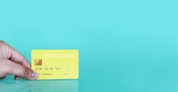 Hand holding a yellow credit card on a blue background, credit card can be used to pay for goods or services, credit card concept, holding credit card clipping path.