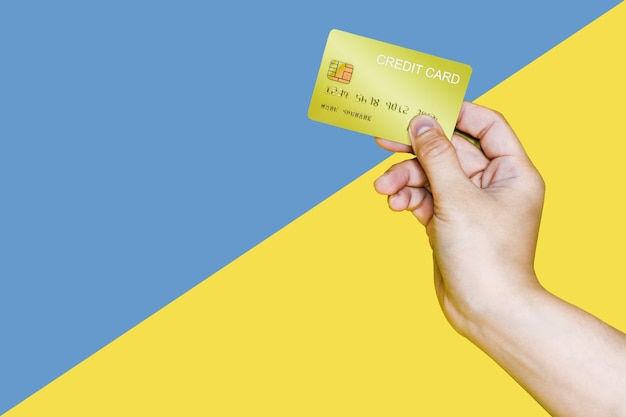 Hand holding a yellow credit card on a blue and yellow background, a hand holding credit card image used in advertising. credit card clipping path.