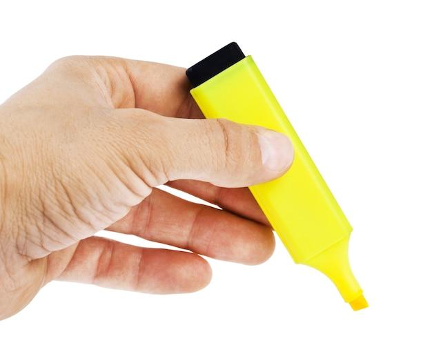 黄色の蛍光ペンを持っている手、白い背景で隔離
