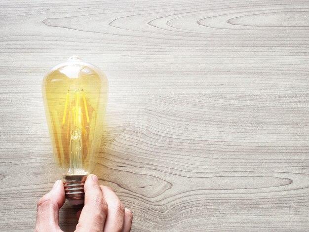 木のテクスチャテーブルに黄色の電球を持っている手コピースペース上面図、インスピレーション経済コンセプト