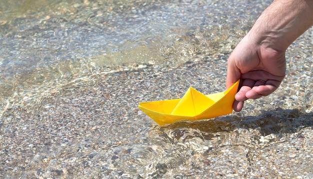 Рука держит желтый бумажный кораблик оригами на поверхности моря