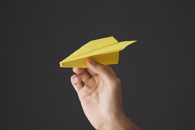 Hand holding yellow paper airplane on gray background.