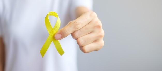 Рука, держащая желтую ленту для поддержки людей, живущих и больных. сентябрь день профилактики самоубийств, концепция месяца осведомленности о детстве, саркоме и раке костей