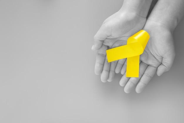 Рука, держащая желтую ленту Premium Фотографии