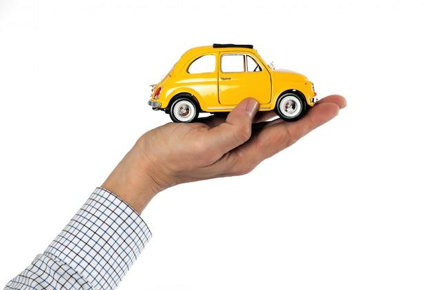Рука держит желтый игрушечный автомобиль