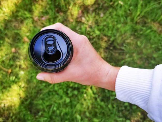 Рука держит черную консервную банку, вид сверху на фоне зеленой травы