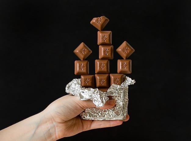Рука держит плитку шоколада в фольге. кусочки шоколада в равновесии. баланс питания.