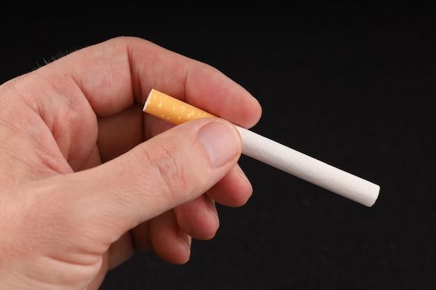 손을 어두운 표면에 담배를 보유