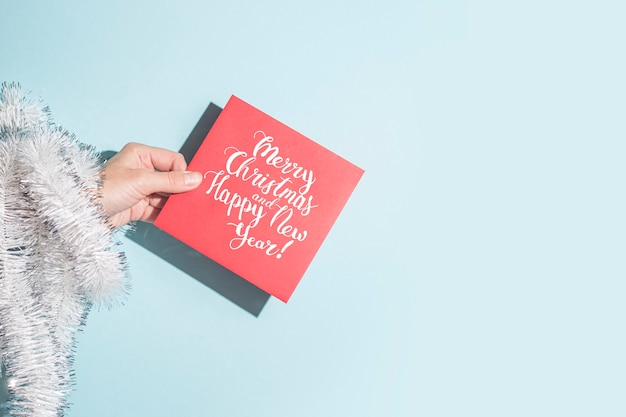 手は青い背景にお祝いの封筒を持っています。ハードシャドウ。