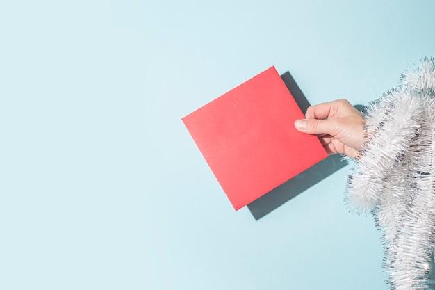 손은 파란색 배경에 축하 봉투를 들고 있습니다. 단단한 그림자.