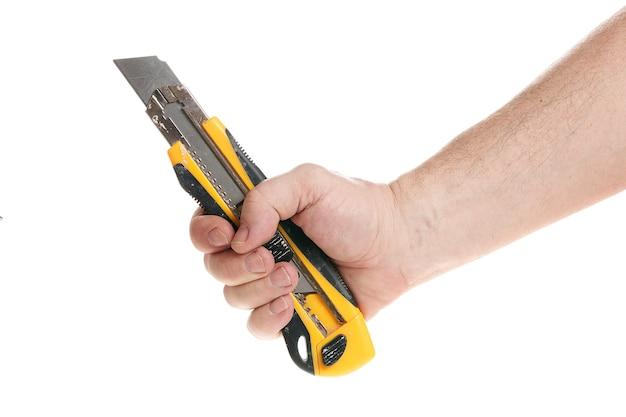 손은 디자이너를 위한 템플릿인 흰색 배경에 건설 칼을 들고 있습니다. 확대