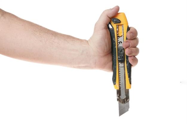 손은 디자이너를 위한 흰색 배경 템플릿에 건설 칼을 들고 있습니다.