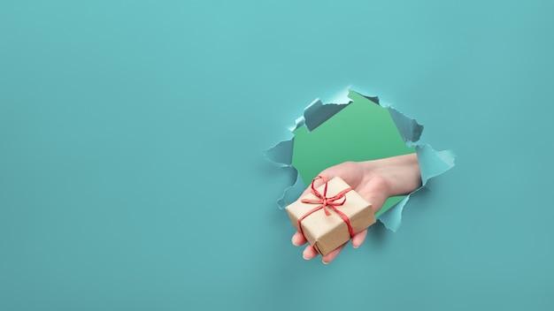 Рука держит подарок ремесла через отверстие в разорванной бумаге.