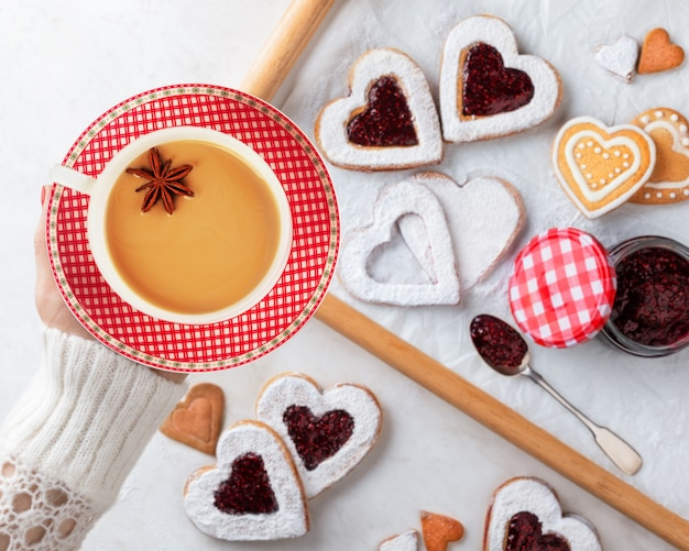 手には、ラズベリージャムと自家製ハート型のクッキーの上に、芳香族スパイスとハーブと紅茶を醸造することによって作られた風味のある茶チャイのカップを持っています。クリスマスやバレンタインデーのコンセプトです。上面図。