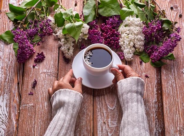 手は、上から木製の背景の景色に咲く春のライラックの花の枝と朝のコーヒーのカップを保持します。フラットレイアンダーグラウンドスタイル。高価な色。花のクリエイティブなデザイン。