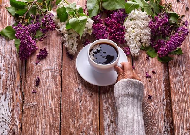 手は、上から見た木の背景に春のライラックの花の枝が咲く朝のコーヒーのカップを持っています。フラットレイアンダーグラウンドスタイル。高価な色。花のクリエイティブなデザイン。
