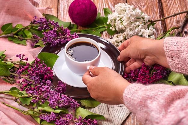 手は、フラット レイアウトの地下スタイルの上から木の背景に咲く春のライラックの花の枝と朝のコーヒーのカップを保持します。