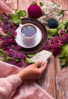 手は、上から見た木の背景に春のライラックの花の枝が咲く朝のコーヒーのカップを持っています。