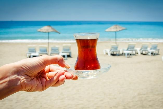 손은 전통적인 터키 차와 컵을 보유하고 있습니다.