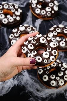 할로윈에 초콜릿 장식으로 장식된 도넛을 손에 들고