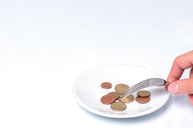 Рука держит вилку с монетами евроцентов на белой тарелке на белом фоне, крупным планом, копией пространства. понятие кризиса продовольственной экономики, социальные проблемы, низкие зарплаты и пенсии, нехватка денег на еду
