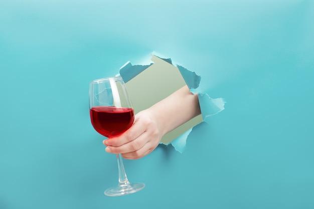 手が破れた穴から赤ワインのガラスを保持しています。イベントのお祝いのコンセプトです。